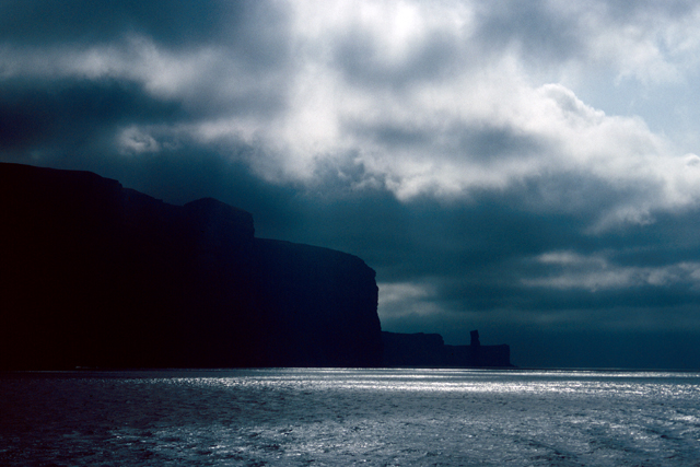 A moody dark sky gathers around the black sighouette of Hoy, in the distance the Old Man of Hoy sea stack sits out from the coastline. Above light breaks through the cloud and is caught by the sea.