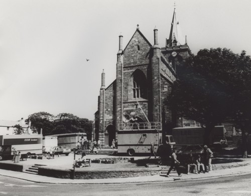 St Magnus Cathedral stands central in this black and white image. Trees shade her. Outside the steps a busy scne, with BBC lorries and outside broadcase units.