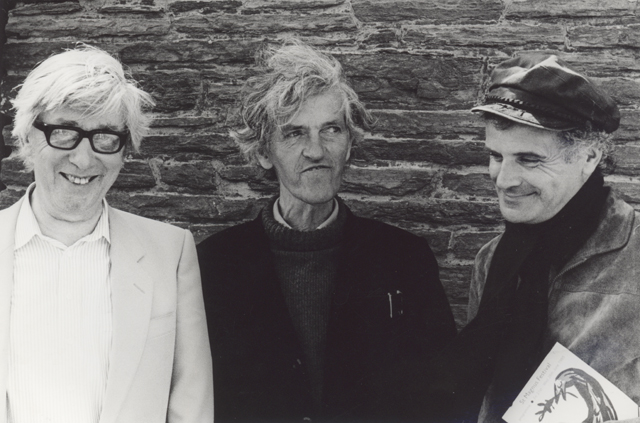 Edwin Morgan white hair windblown beside George Mackay Brown grey hair windblown beside Peter Maxwell Davies in a hat and clutching a St Magnus Festival programme.
