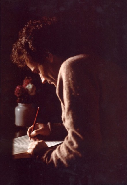 With the only light coming from a window, a man bends over a manuscript with his red pencil. In a stoneware jar on his desk some red flowers. The image is just these elements: man, pencil, flowers, window light.