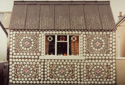 A shed is encrusted with shells in repeated patterns. Scallop shells give bold rectangular frames and a central circular design. In the house's only window hang three tiny lifebelts.