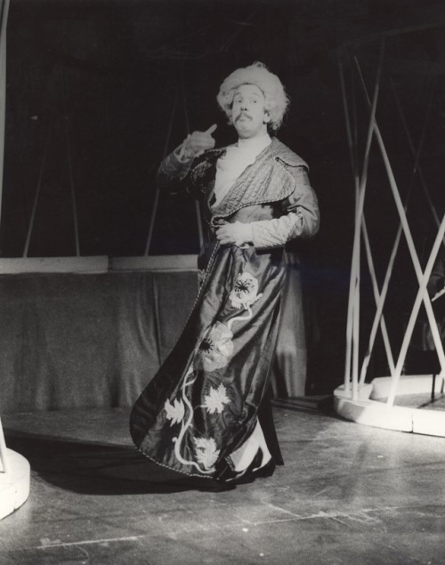 A man on stage in a wig and a silk embroidered house coat, his coat swings at the bottom, he has just spun round. He holds his hand up and indicates someone drinking perhaps, his eyes wide and his mouth downturned.