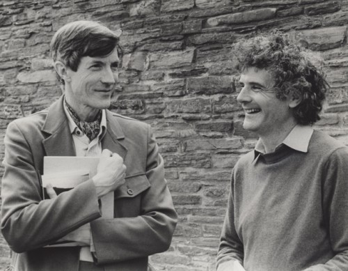 Two men Richard Murphy and Peter Maxwell Davies talk. Behind them a high stone wall. Richard, a tall man is on the left and he clutches to his chest papers, maybe a manuscript.