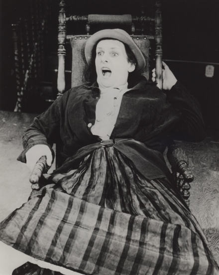 An actress on stage in a rocking chair screaming and hands clasping the chair arm and back, she shows fear in her face. The costume looks early 20th century