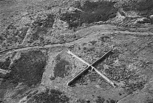 In this black and white aerial photograph, a huge stone X sits like a kiss at the end of a love letter on the rough moorland.