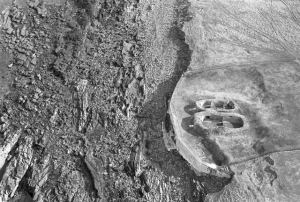 Black and white aerial photograph of the Knap of Howar, Papa Westray. The images shows the dwellings on the right with the coastline cutting the image in two.