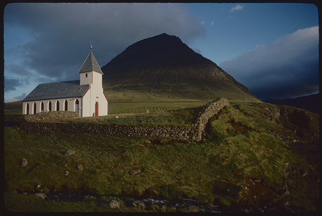 A crisp white church with slate steeple sits at the foot of a sharp steep mountain, spire and peak echo each other.