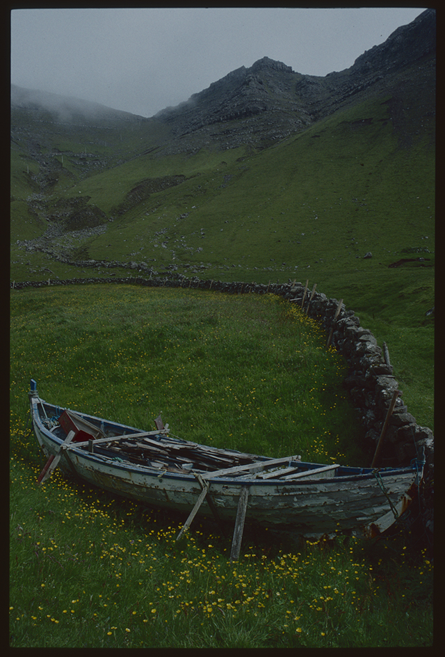 In a meadow beside a stone dyke a rotting boat is piled with wood. The boat is propped up, someone is looking after it. The winding wall leads us into the distance to high mist shrouded hills.