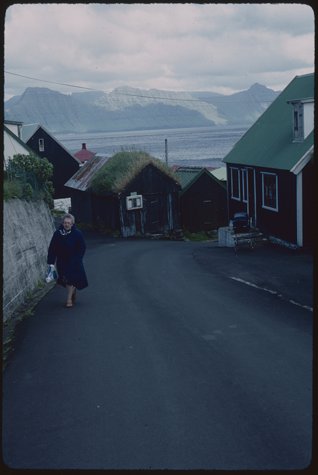 A lady in dark coat and bright shoes makes the climb up the steep tarmaced hill, in her had a carrier bag. Clinging the roadside are faroese houses, black and dramatic with bright coloured roofs.