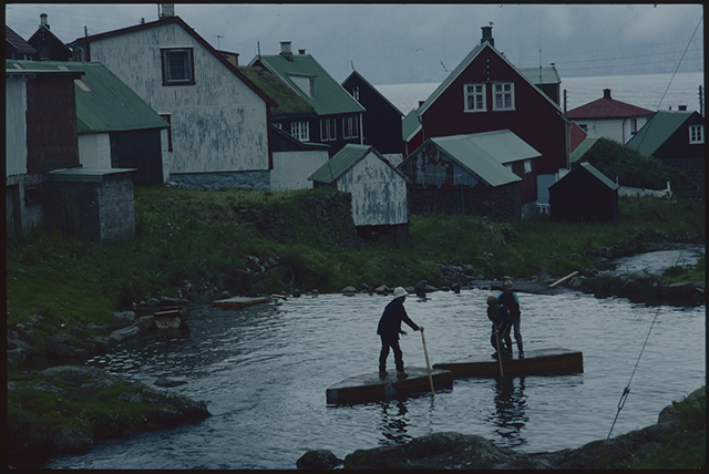 In the water below the coloured shapes of roofs and the black and white of gable ends, three boys punt on a homemade raft.