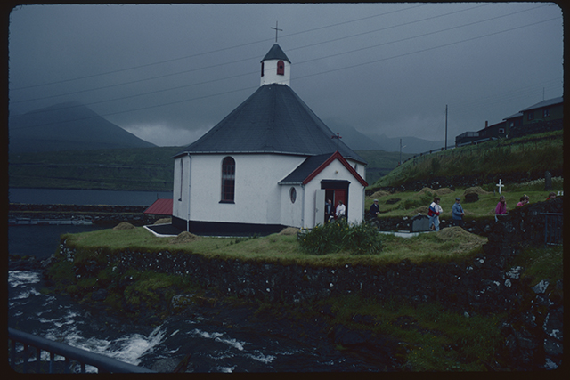 A small round church with central steeple defiantly stands on a small patch of land inches aaway from the sea. The congregation are leaving, a conversation is happening at the door.
