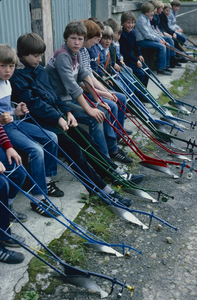 A line of boys sit with their brightly painted miniature ploughs, they are waiting to be judged.