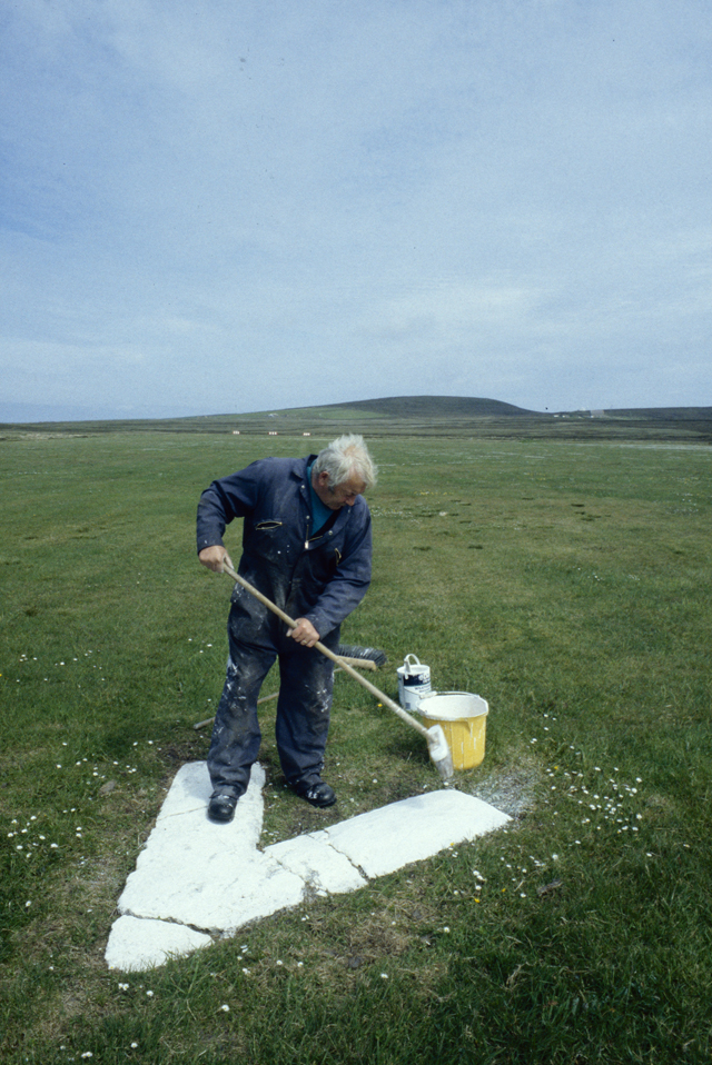 In a green field a man paints a giant white chevron, it is the island airport runway.