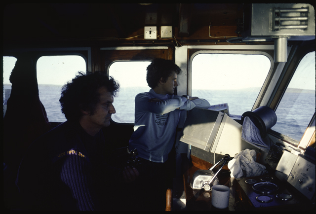 Two men, a young lad and one older, stare ahead out of the pilot house of their boat.