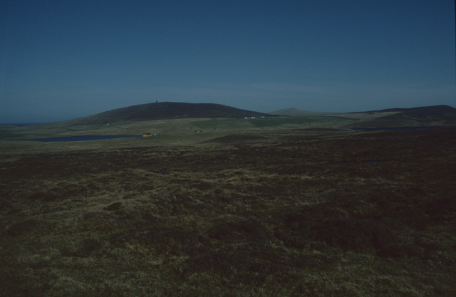 A dark moorland looking peat rich and a low hill in the background with a loch at its feet.