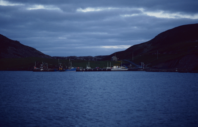 An evening settles over a harbour with boats nestled in dark hills.