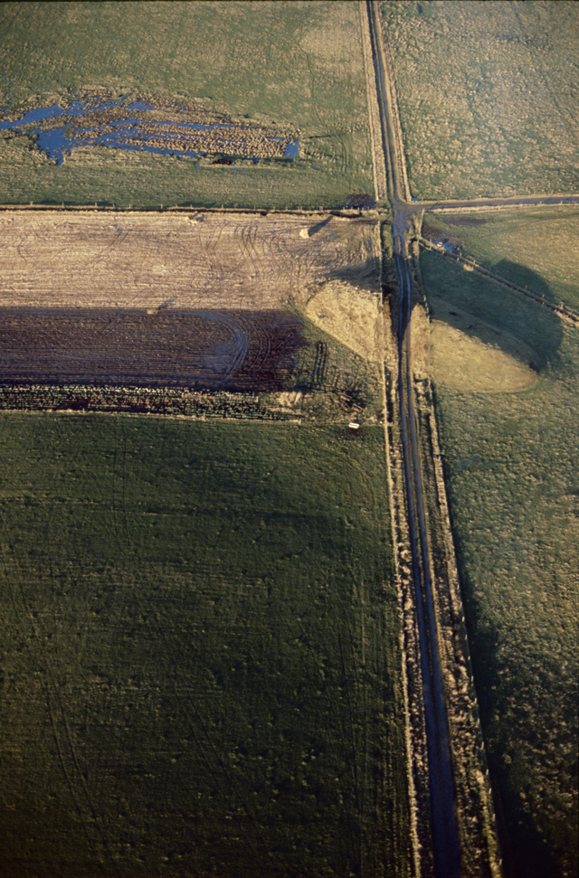 Aerial photograph of a road cutting through a mound, a long stratigh road lit warmly by the low sun.
