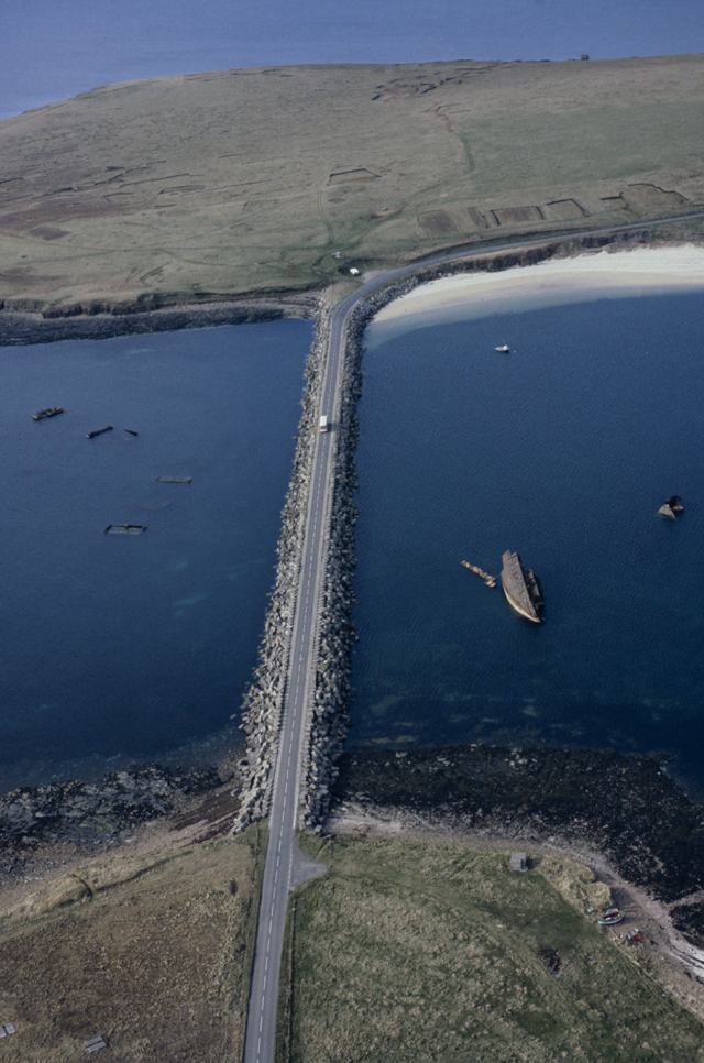 Aerial photograph of a causeway stretching betwen two green islands, a white beach reaches off to the right top hand corner of the image and in the sea rusts a massive hulk of a blockship.