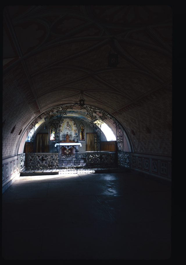 The darkness of the top and bottom of this image is cut through by the luminous alter at the Italian Chapel, light from the curved wall window picking up detail of the decorated chapel.