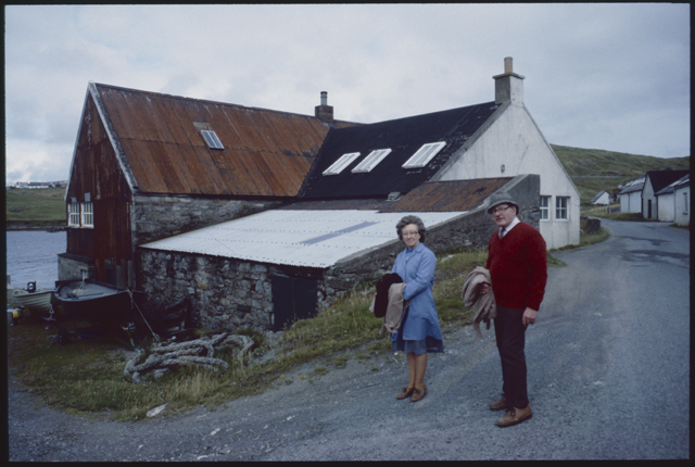 A man and woman stop and turn to the camera behind them the coureggated iron roof of a shed meet anothe iron roof and joins with the black roof of a house, the shapes and angles are emphasised by the steep road they stand on.