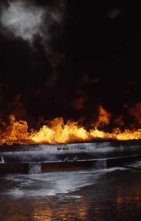 A curve of fire contained by a rim of steel lights a cloud of white smoke amongst the black. The white foam used in fighting the fire gives a texture to the lower part of the frame and picks up on the white patch of smoke top left.