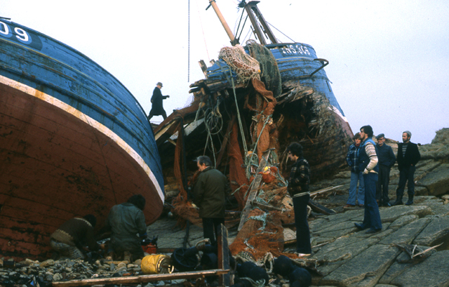 A figure strides betwen two sections of a shipwrecked boat, he is dwarfed by its size. People gather to look at the debris, the white stripe of the boats hull leads you into the sentre of the image.