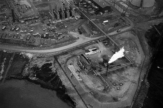 This black & white image of construction of the oil terminal is interuppted by the white flash of the lit flare.