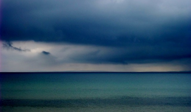 Moody blue sky of deep dark cloud comes to a sharp navy blue horizon over blue-torquoise waters of Scapa Flow