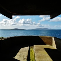 The view of cloudlets and the summer blue sea reflecting the sky with low hills behind is all tightly framed in the 'window' of the war building. The dark shadows of the interior and cut through with a shaft of light creating an angled shape echoing the 'window'.