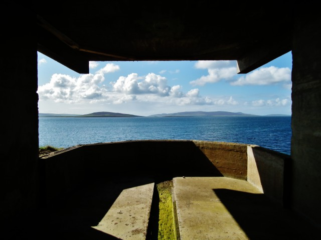 The view of cloudlets and blue summer sea with low hills is framed in the look out of a war building, black, hard edged, angled shapes, sun entering the interior leaves a bright shape like a jogsaw piece fitting the shape of the 'window'.