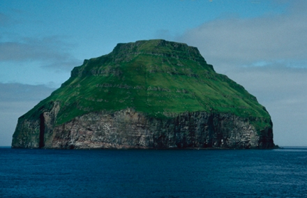 An almost conical island sits mid framne in the sea, rich greebn grass gives a velvet look to the rough isle.