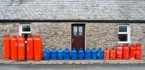 Gas bottles line against a house, they have been almost lovingly arranged, red big gas bottles bookend a line of small blue ones.
