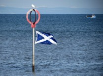 A red marker stands in the sea, on top of it a gull sits, the marker is also a flagpole flying the Saltire.