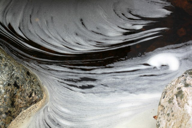 White frothed water swirls in a stream creating a feathered texture as it navigates a stone.