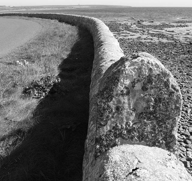 A decorated stone wall dominates the foreground and curves off to the left, the stong black shadow clings to it in this black & white photograph.