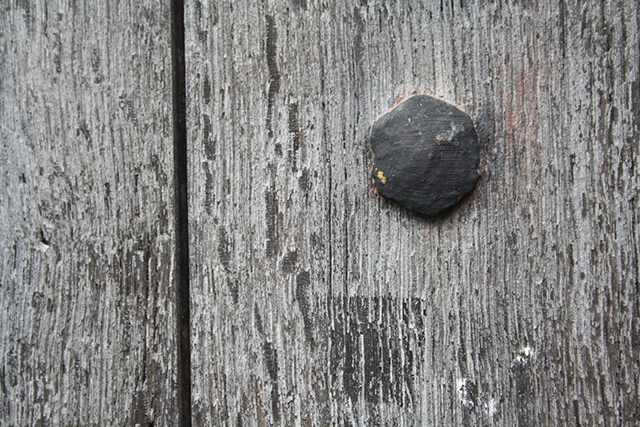 An iron nail head sits hexagonal in the textured surface of a door or maybe a gate. The image is composed of three elements, the texture, the hexagonal black shape and the black line of shadow between two planks. This image is almost monochrome, haunted only by a faint echo of paint flecks.