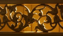 A wrought iron rail, backlit in a warm glow, flourishes with detail