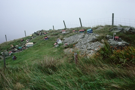 A miniature Faroese village of tiny brightly coloured model houses clings to a rocky mound in a field in Shetland.