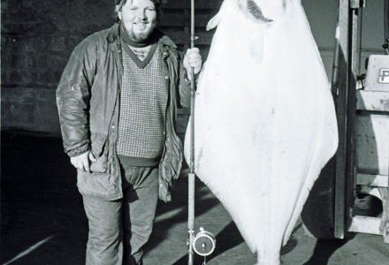 A man stands dwarfed by the gigantic fish he has caught. The vast white underside of a halibut takes up more than half of the frame of this portrait.