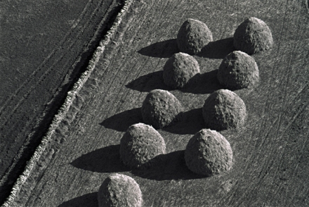 An aerial black and white photograph of oat stacks9 sit in two rows, the low sun casts a dark shadow from each stack and they look loke buttons on a military jacket.