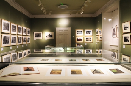 Display case with Gunnie's cameras, film rolls, print boxes and projector