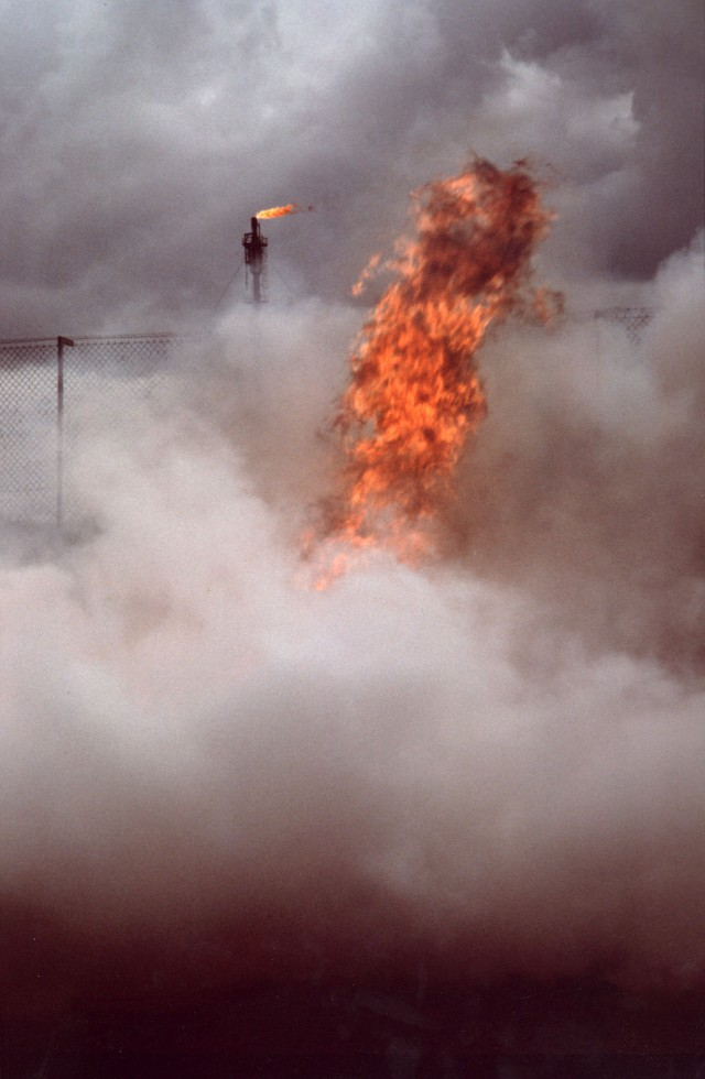 A smoke filled image with a blaze of flame, red and hot against the grey-white smoke, and in the distance the talk firey tip of the Flotta Flare.