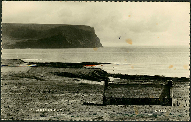 A browning postacrd showing a croft house faceing the North Atlantic, the image is balanced with the house in the bottom right and the bulking dark of the Kame of Hoy top left.
